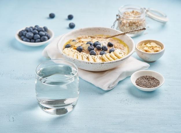 Glas trinkwasser und frühstück der gesunden diät mit hafermehl Premium Fotos