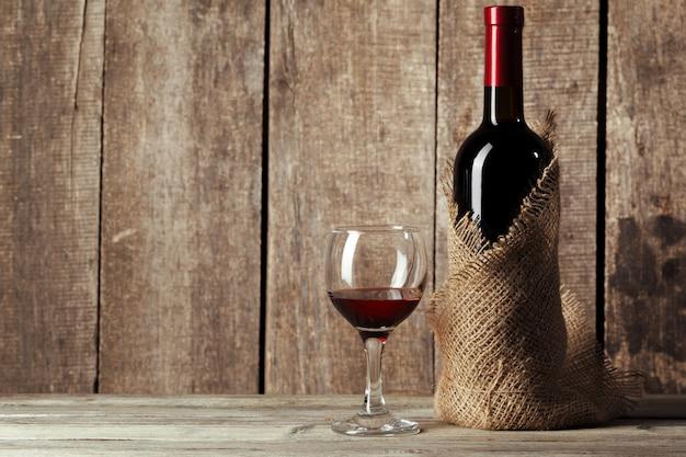 Glas und flasche mit köstlichem rotwein auf tabelle gegen hölzerne wand Premium Fotos