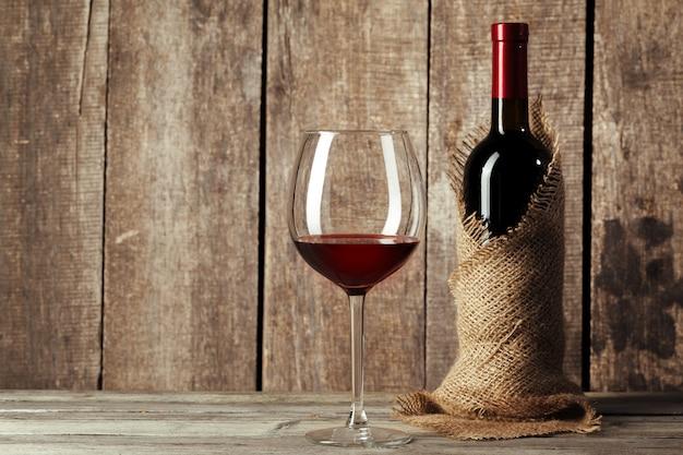 Glas und flasche mit köstlichem rotwein auf tabelle gegen holz Premium Fotos