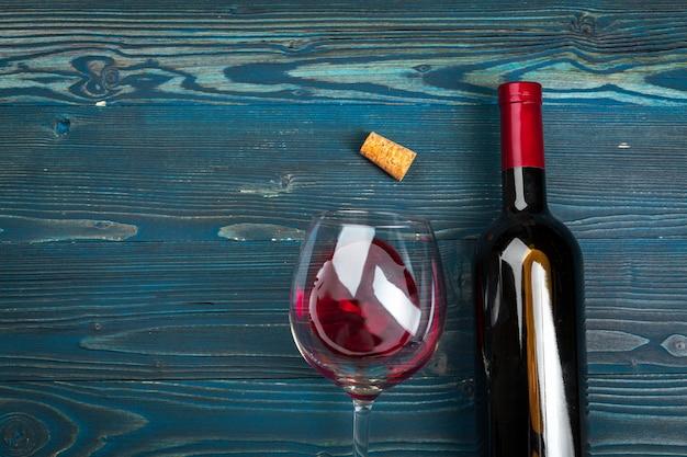 Glas und flasche mit rotwein auf hölzernem hintergrund, draufsicht Premium Fotos