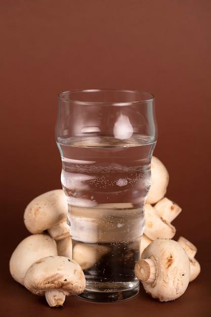 Glas wasser, umgeben von frischen pilzen Kostenlose Fotos