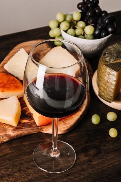 Glas wein nahe trauben und käse Kostenlose Fotos