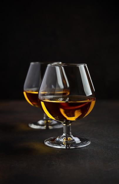 Glas weinbrand oder kognak auf dem alten rostigen hintergrund. Premium Fotos