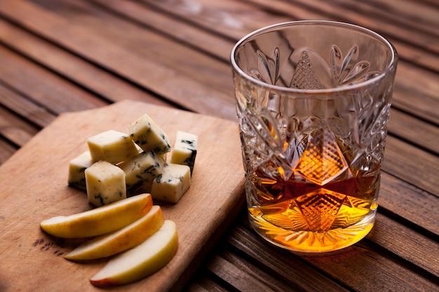 Glas whisky auf einem holztisch mit einem snack Premium Fotos
