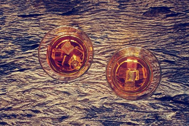 Glas whisky bourbon mit eis auf hölzernem beschaffenheitshintergrund. Premium Fotos