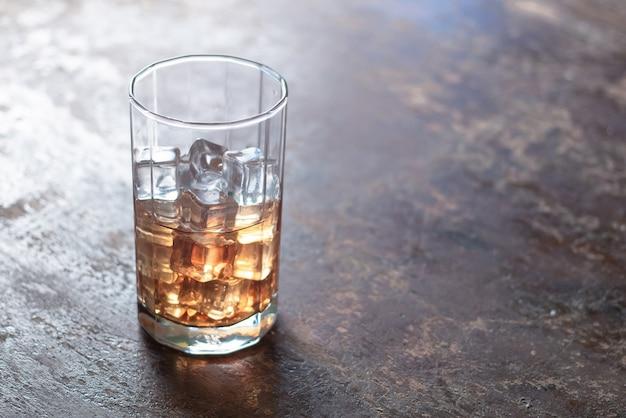 Glas whisky mit eis auf schwarzem hintergrund Premium Fotos