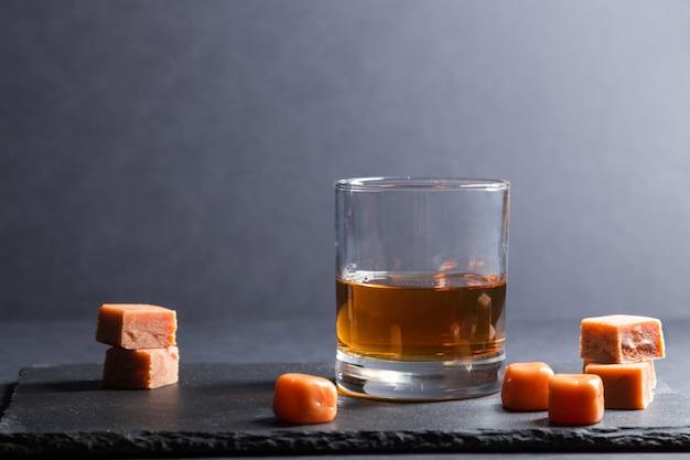 Glas whisky mit karamellbonbons auf einem schwarzen steinschieferbrett auf schwarzer oberfläche. seitenansicht, kopierraum. Premium Fotos