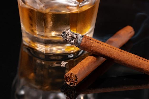 Glas whisky und brennende zigarre auf schwarzem hintergrund Premium Fotos