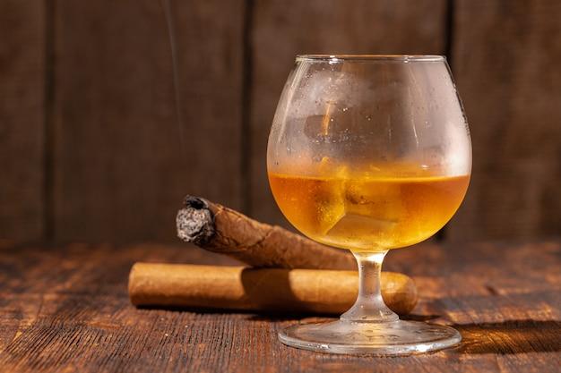 Glas whisky und brennende zigarre in einem aschenbecher auf holz Premium Fotos