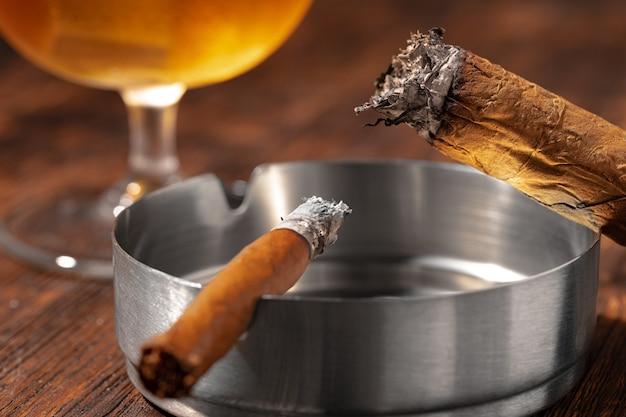 Glas whisky und brennende zigarre in einem aschenbecher Premium Fotos