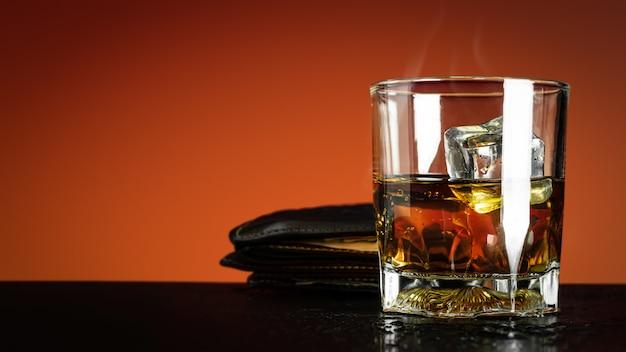 Glas whisky und eiswürfel auf rot Premium Fotos