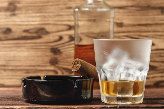 Glas whisky und gerollte zigarren auf holztisch Premium Fotos