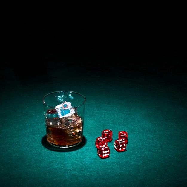 Glas whisky und rote würfel auf grüner kasinotabelle Kostenlose Fotos