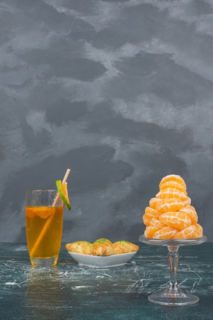 Glas zitronenwasser mit teller mit süßer bäckerei und mandarinenscheiben. Kostenlose Fotos