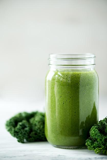 Glasbecher mit grünem gesundheitssmoothie, kohlblättern, kalk, apfel, kiwi, trauben, banane, avocado, kopfsalat. roh, vegan, vegetarisch, entgiftung, alkalisches lebensmittelkonzept. Premium Fotos