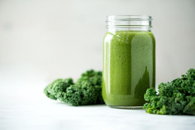 Glasbecher mit grünem gesundheitssmoothie, kohlblättern, kalk, apfel, kiwi, trauben, banane, avocado, kopfsalat. Premium Fotos