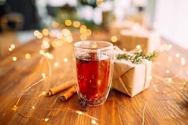 Glasbecher schwarzer tee mit sternanis auf dem hölzernen festlichen tisch mit girlandenlichtern Premium Fotos