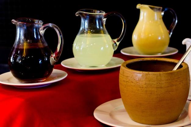 Glasdekanter mit granatapfelsauce, zitronensauce und senf. ton gelber topf Premium Fotos