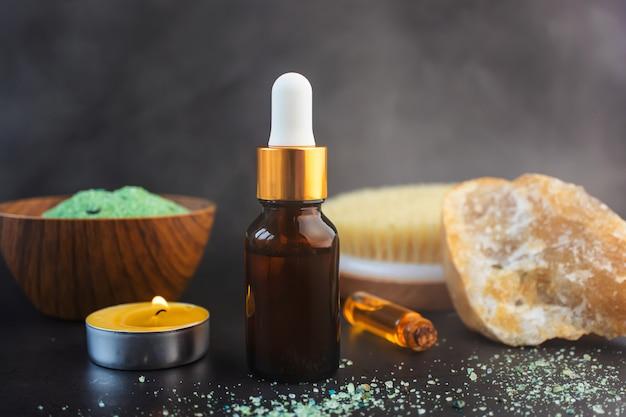 Glasflasche mit pipette, kerze, kleiner flasche ätherischem öl, naturbürste und zierstein im dunkeln dampf - in der luft das konzept kosmetischer eingriffe in bad, dampfbad, sauna Premium Fotos