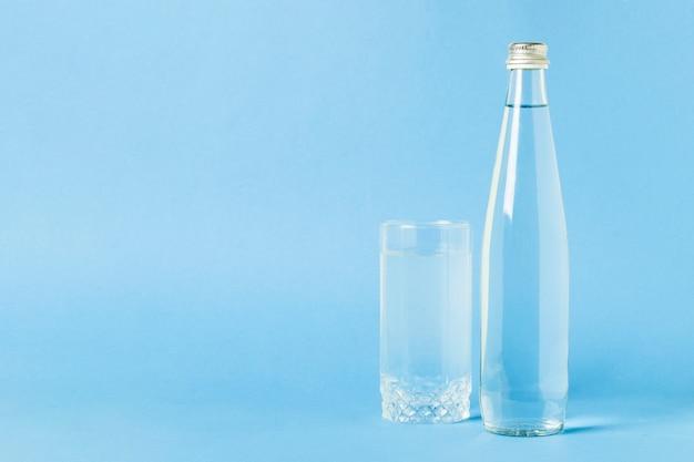 Glasflasche und glas mit haarscharfem auffrischungswasser auf einer blauen oberfläche. konzept von schönheit und gesundheit, wasserhaushalt, durst, sommer Premium Fotos