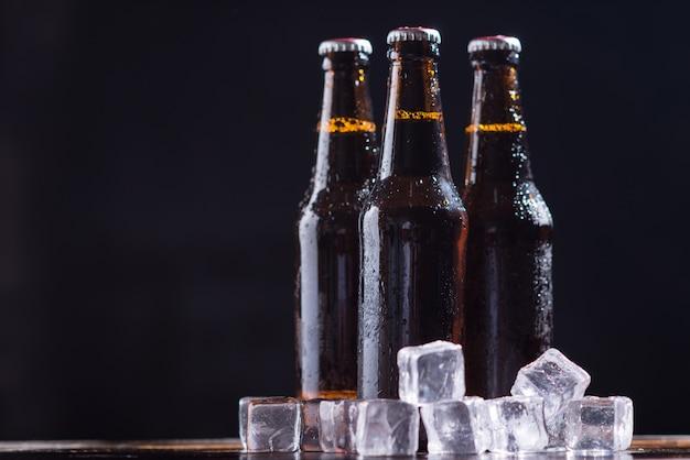 Glasflaschen bier mit glas und eis auf dunklem hintergrund Kostenlose Fotos