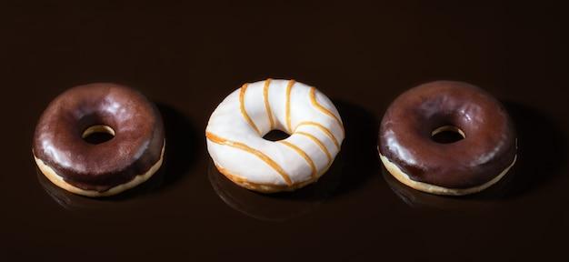 Glasierte donuts auf dunkler schokolade glatten hintergrund Premium Fotos