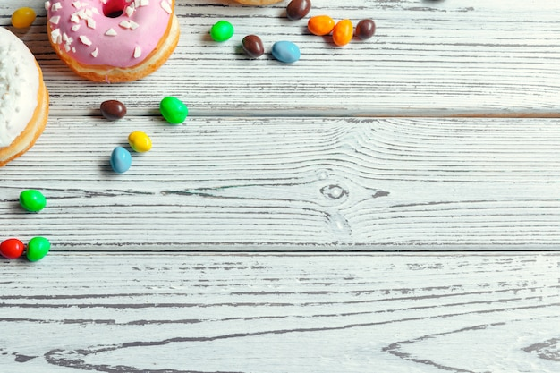 Glasierte schaumgummiringe auf hölzernem hintergrund Premium Fotos