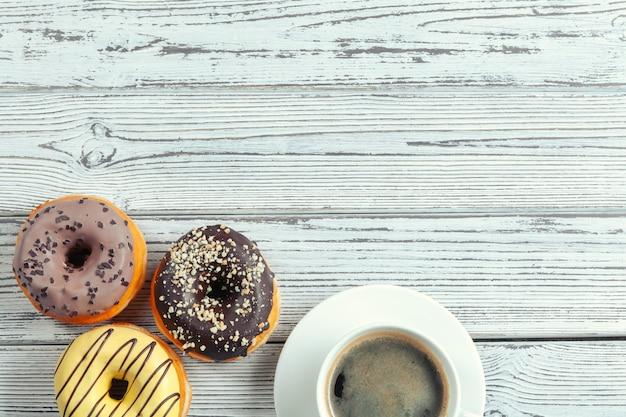 Glasierte schaumgummiringe auf holzoberfläche mit kaffeetasse Premium Fotos