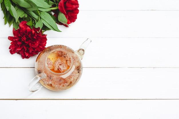Glaskessel kräutertee mit frischen blumen nah oben Premium Fotos
