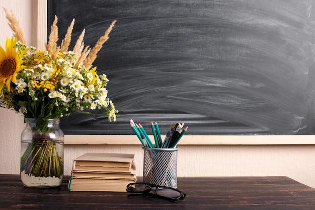 Glaslehrer bücher und wildblumen bouquet auf dem tisch, tafel mit kreide. das konzept des lehrertages. kopieren sie platz. Premium Fotos