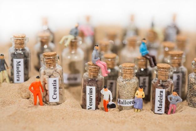 Glasreagenzglas mit sand verschiedener sommerferienorte. das hotel liegt im sand mit kleinen figuren. Premium Fotos