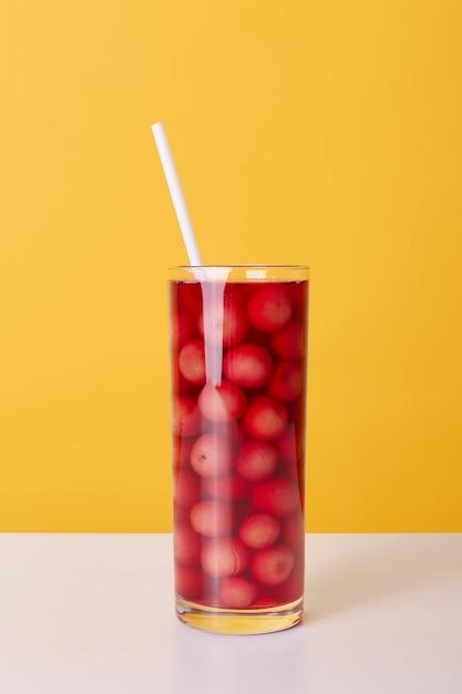 Glasschale des roten cocktails mit trinkröhre und kirschen lokalisiert über gelbem hintergrund, frisches alkoholfreies sommergetränk auf tisch. Kostenlose Fotos