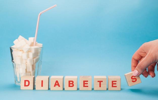 Glasschale mit einem strohhalm voller würfel weißzucker. blockieren sie buchstaben von diabetes in einem kreuzworträtsel. Premium Fotos