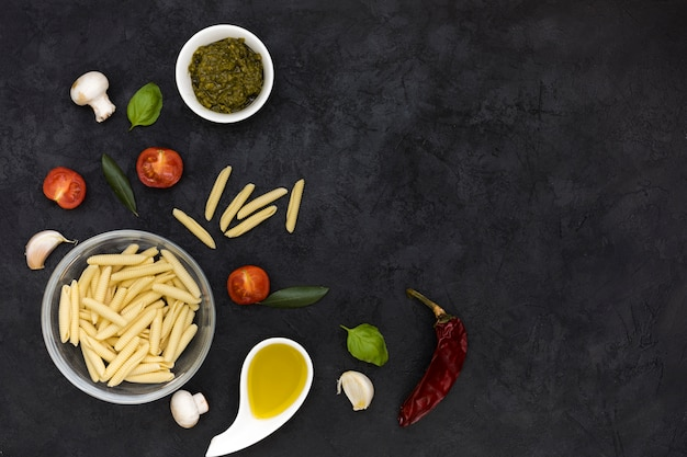 Glasschale mit garganelli-nudeln mit sauce; pilz; basilikum; tomaten; roter chili und knoblauchzehe auf schwarzem strukturiertem hintergrund Kostenlose Fotos