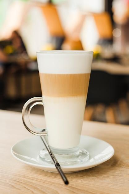 Glasschale mit heißem latte auf holztisch an der cafeteria Kostenlose Fotos