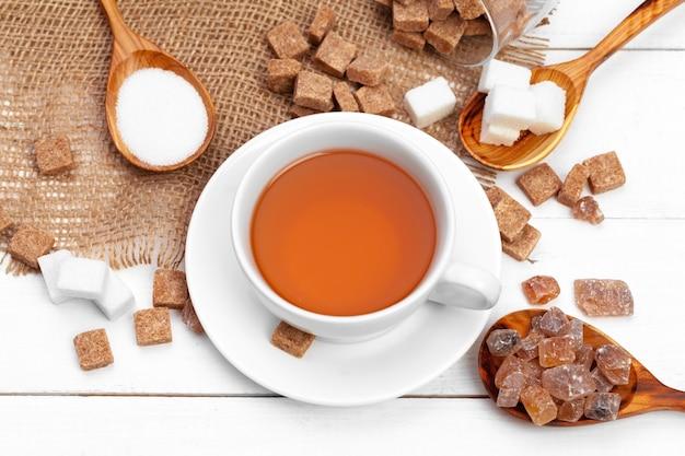 Glastasse heißer tee mit zucker auf dem tisch Premium Fotos