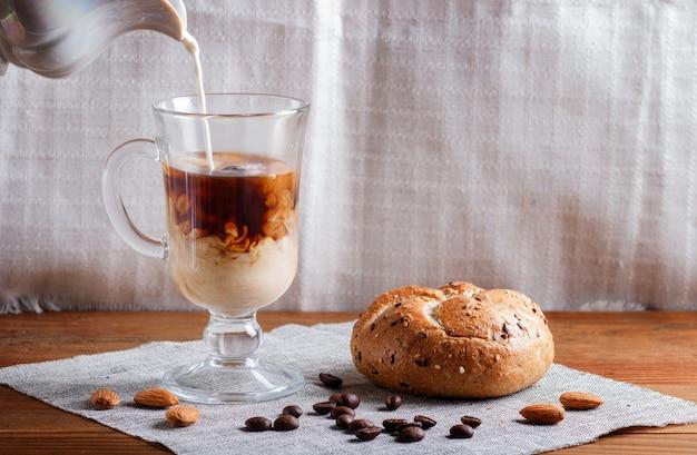 Glastasse kaffee mit sahne goß vorbei und brötchen auf einem hölzernen hintergrund und einem leinengewebe Premium Fotos