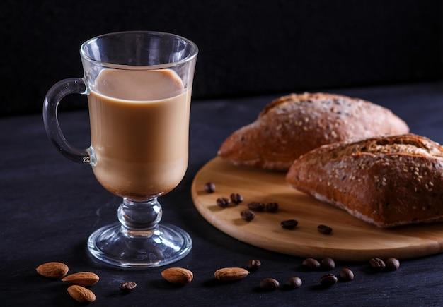 Glastasse kaffee mit sahne und brötchen auf einem schwarzen hintergrund Premium Fotos