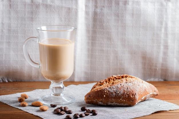 Glastasse kaffee mit sahne und brötchen Premium Fotos