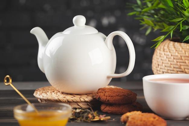 Glasteekanne mit schale schwarzem tee auf holztisch Premium Fotos