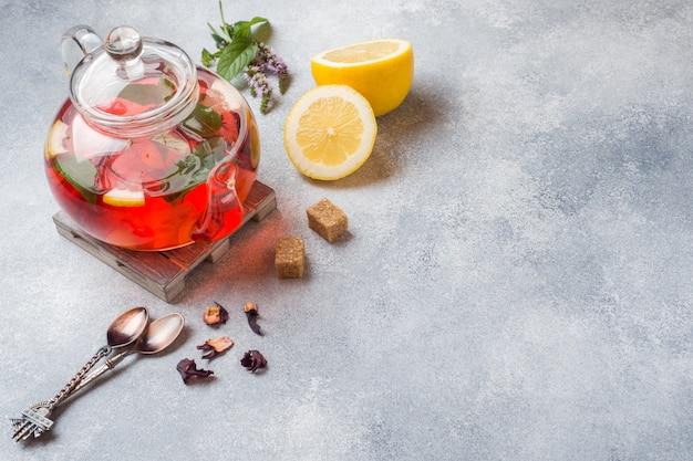 Glasteekanne mit tee, minze und zitrone auf grauer tabelle mit kopienraum Premium Fotos