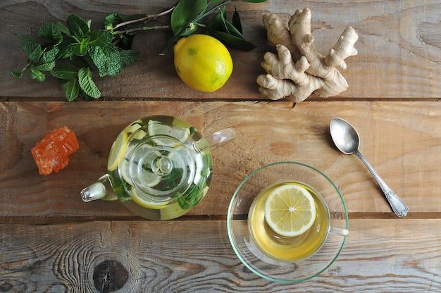 Glasteekanne und glasbecher tee mit ingwer und zitrone und minze auf rustikalem hölzernem hintergrund Premium Fotos
