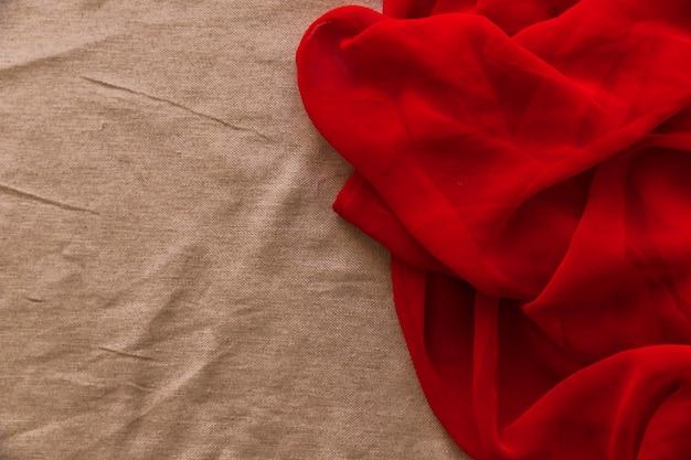 Glattes rotes gewebe auf braunem gewebehintergrund Kostenlose Fotos