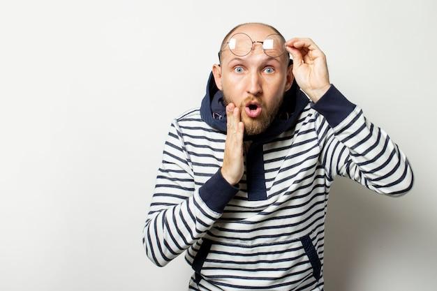Glatzköpfiger junger mann mit bart, pullover mit kapuze auf der stirn mit einem überraschten gesicht auf isoliertem weiß. geste der überraschung, des schocks. speicherplatz kopieren Premium Fotos