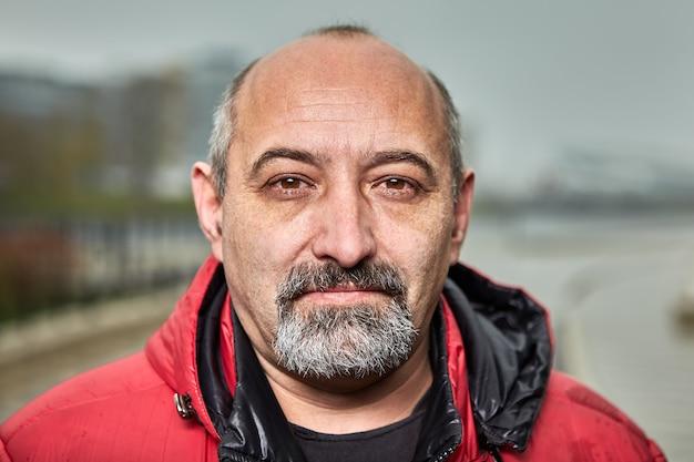 Glatzköpfiger reifer bärtiger mann in der roten jacke. Premium Fotos