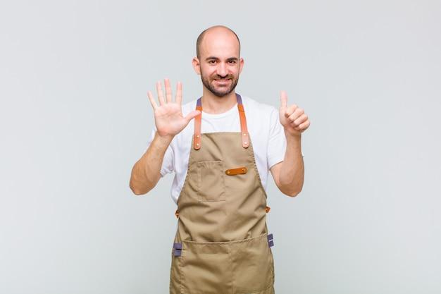 Glatzkopf lächelnd und freundlich aussehend, nummer sechs oder sechst mit der hand nach vorne zeigend, countdown Premium Fotos
