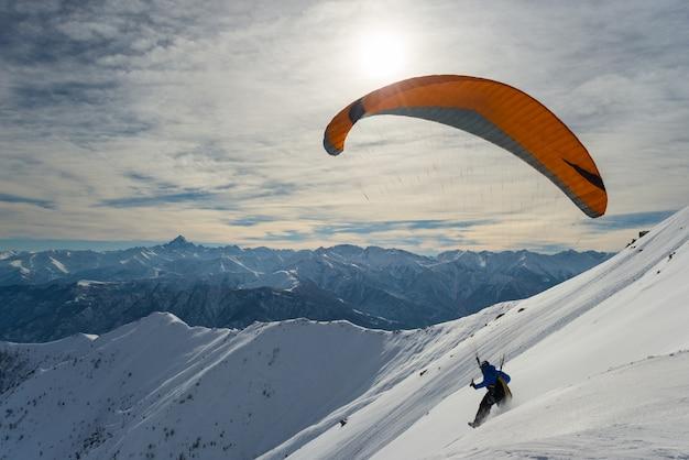 Gleitschirm, der von der schneebedeckten steigung startet Premium Fotos