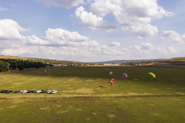 Gleitschirm silhouette fliegt über schöne grüne landschaft unter blauem himmel mit wolken. Kostenlose Fotos