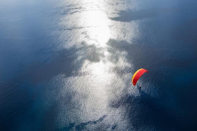 Gleitschirmfliegen am himmel. fliegen über den atlantik mit blauem wasser an hellem sonnigem tag. luftaufnahme des gleitschirms auf der insel madeira, portugal. extremsport. Premium Fotos
