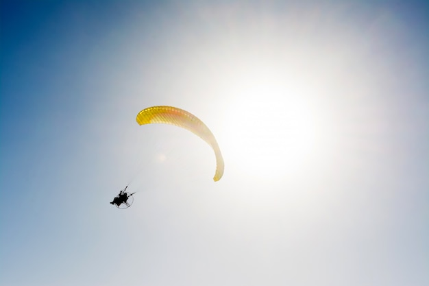 Gleitschirmfliegen mit paramotor auf blauem himmel Premium Fotos